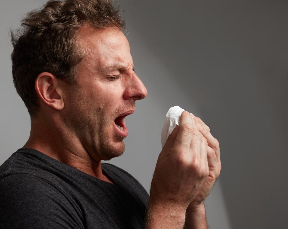 Mann niest